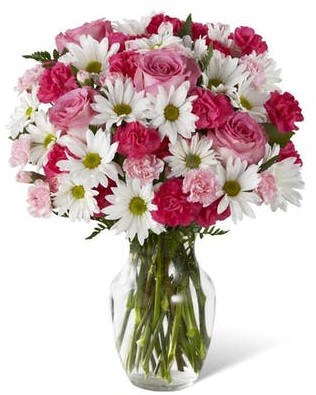 "Our Sweet Surprise bouquet is always a favorite. Pink mini carnations along with traditional white daisies and greenery are presented in a classic clear vase.   Approximately 15""h x 13""w"